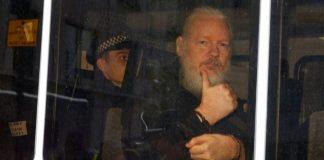 លោក Julian Assange លើកមេដៃនៅក្នុងឡានប៉ូលិស។ Credit: REUTERS